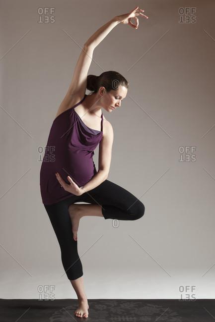 Pregnant women doing yoga tree pose and bending to side, Boston, Massachusetts, USA