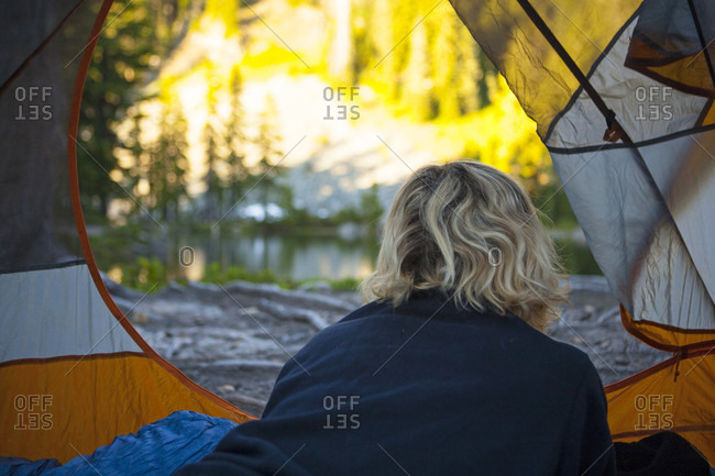 Rear view of blonde girl looking out from tent, Snoqualmie, USA