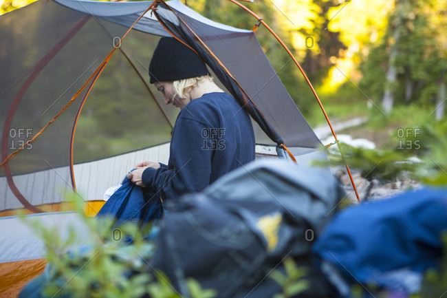... USA Side view of blonde woman sitting in tent at sunset Snoqualmie USA & view from tent stock photos - OFFSET