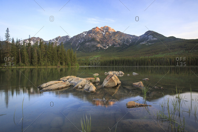 Pyramid Mountain glows orange and is reflected in Pyramid Lake at sunrise in Jasper National Park, Alberta, Canada.