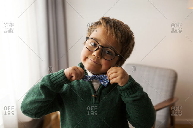 Little boy with glasses adjusting his bowtie