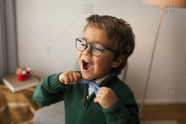Silly boy with glasses adjusting his bowtie