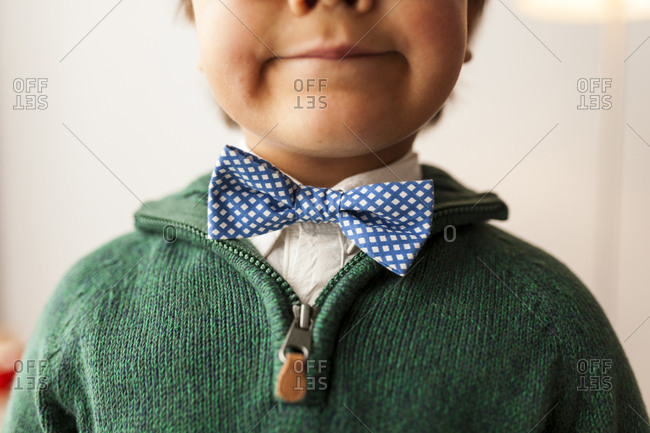 Close up of a boy wearing a green sweater and bowtie
