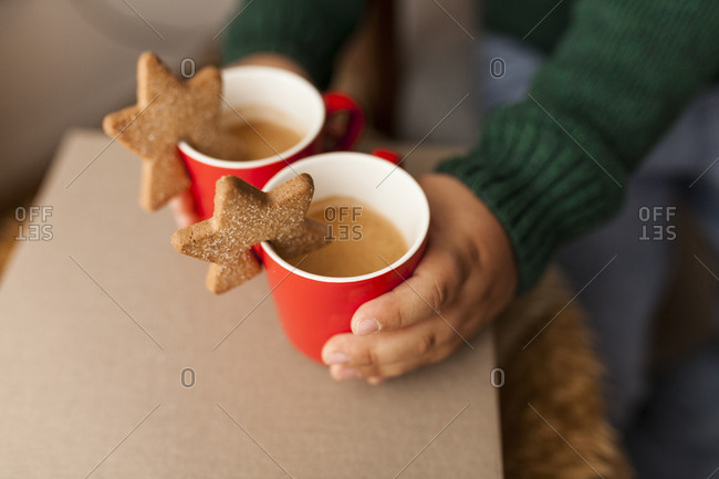 Young boy grabbing two warm drinks with star cookies