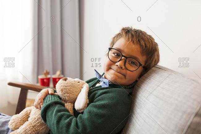Boy wearing green sweater holding a stuffed animal