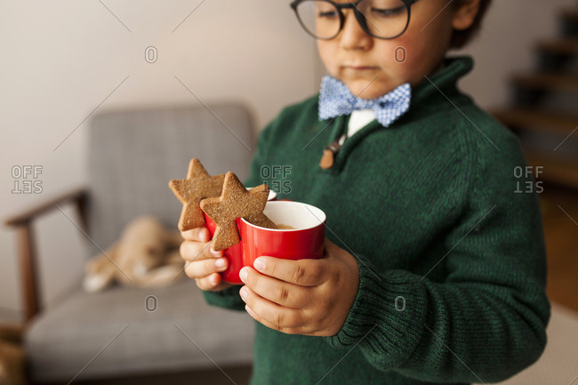 Little boy with glasses holding two warm drinks with star cookies