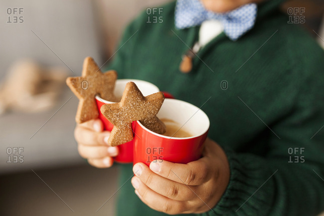 Boy holding two warm drinks with star cookies