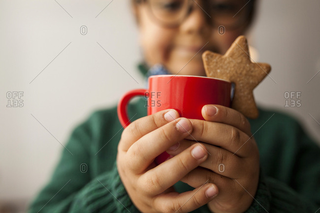 Young boy with glasses holding a warm drink with star cookie