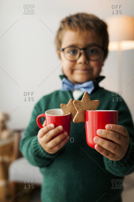 Young boy with glasses holding two warm drinks with star cookies