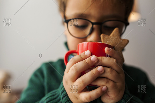 Little boy with glasses drinking a warm drink with star cookie