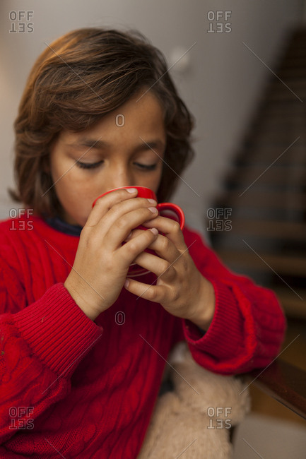 Boy drinking warm beverage