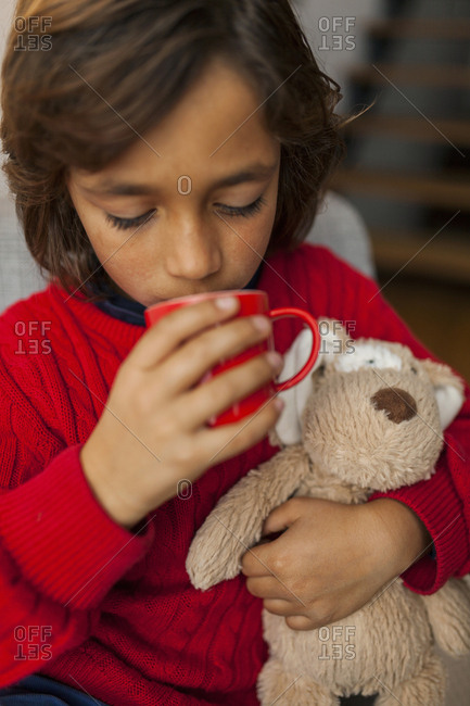 Boy holding stuffed animal and drinking warm beverage