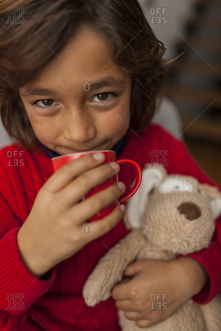 Boy drinking warm beverage and holding stuffed animal