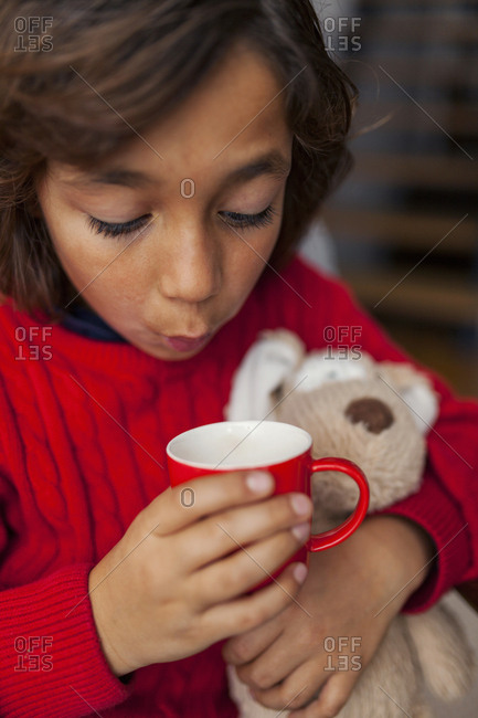 Little boy blowing on warm beverage and holding stuffed animal