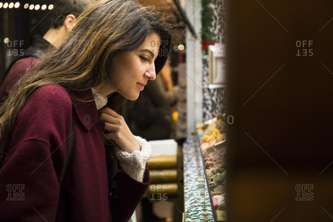Beautiful young woman in red coat standing near stall at marketplace and choosing goods for buying.