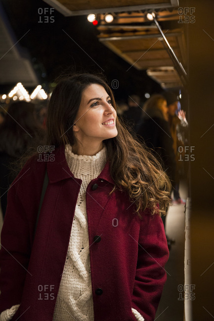 CheerfulĘyoung woman in red coat walking at marketplace in evening and looking at stalls.