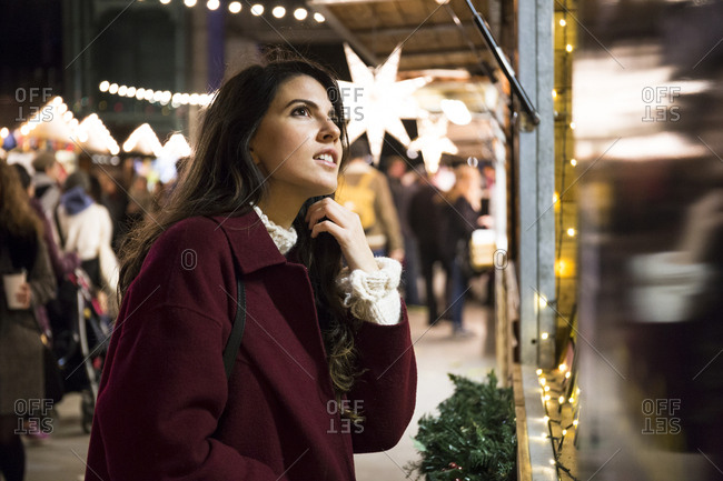 Lovely young woman in red coat standing near stall at marketplace and looking at goods.
