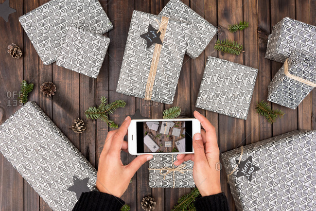 Woman taking a picture of handmade craft christmas gifts on the table