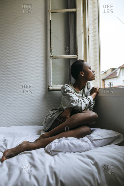 Woman sitting on a bed looking out the window