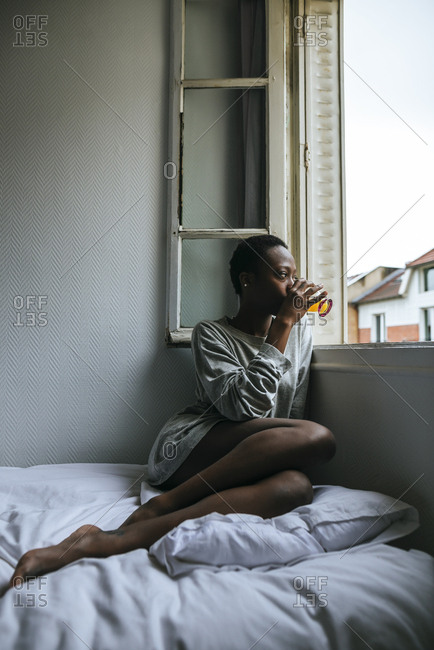 Woman sitting on a bed drinking juice and looking out the window