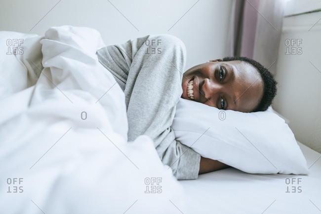 Young woman lying down smiling in bed in her room