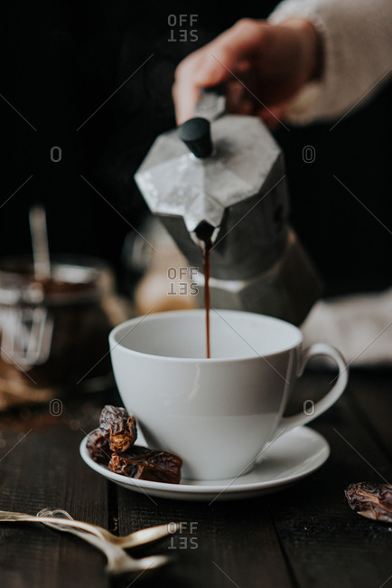 Pouring coffee from stovetop coffee maker in a white cup
