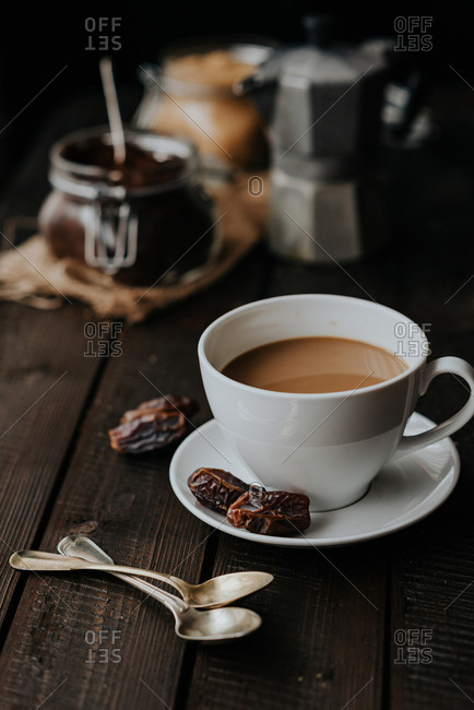 Cup of black coffee with milk on a wooden background served with dates fruit