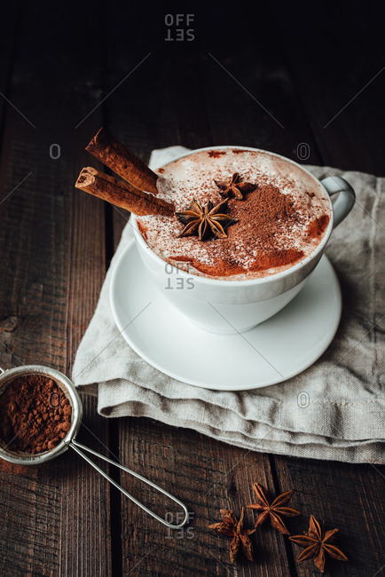 Cup of hot cocoa with cinnamon and anise on a dark wooden background