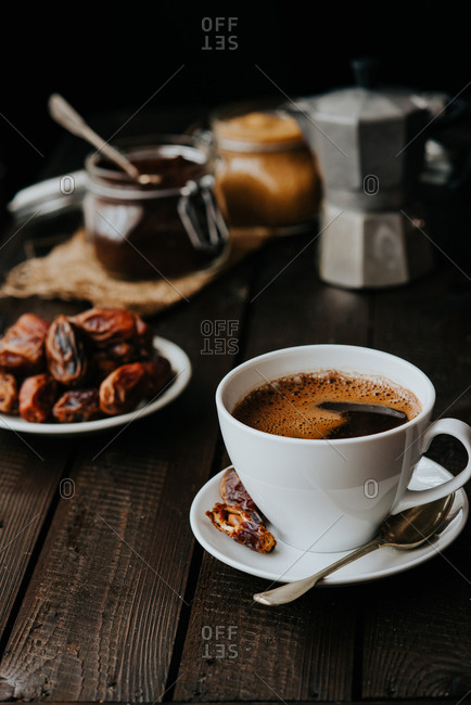 Cup of black coffee on a wooden background served with dates fruit