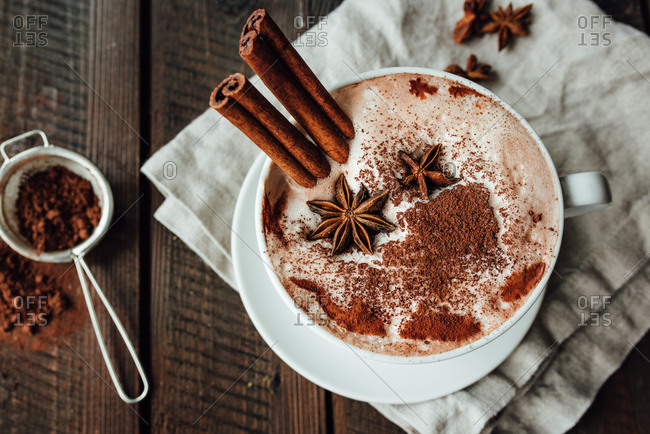 Overhead shot of hot cocoa in white cup with cinnamon and anise inside the cup