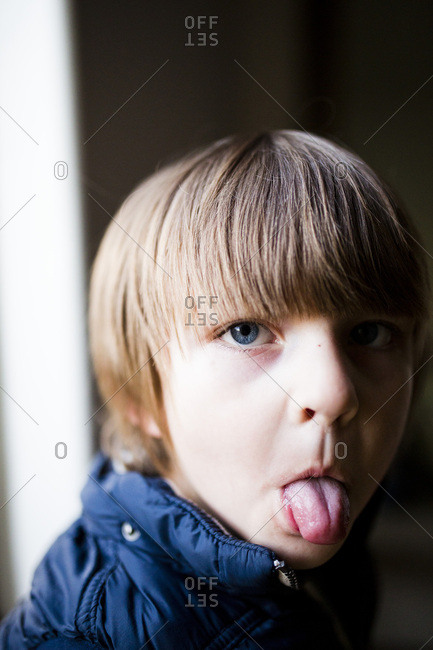 Portrait of young boy sticking tongue out