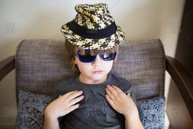 Young boy wearing a straw hat and sunglasses