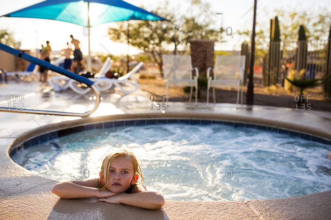 Serious young girl sits in a hot tub