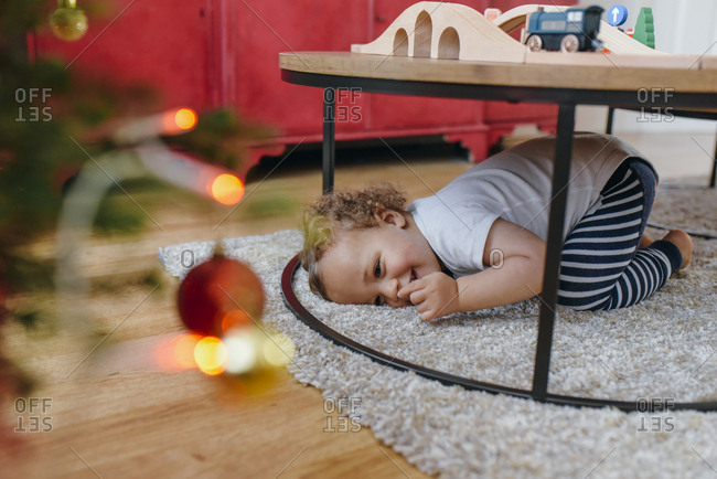 Young boy playing underneath a coffee table
