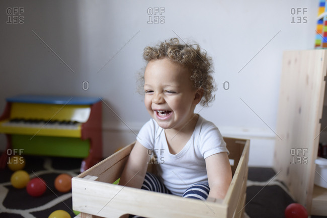 Young boy laughing and playing in a wooden crate