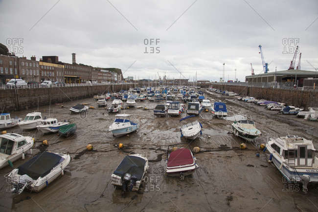 Island of Jersey, Channel Islands - November 30, 2017: Boats moored in low tide at Marina harbor