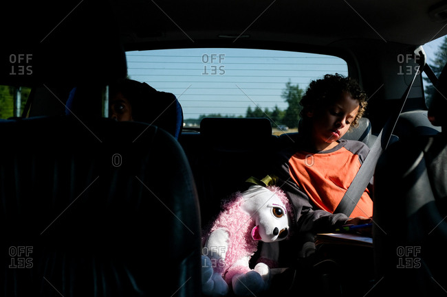 Sleepy boy riding in backseat of car with stuffed animal