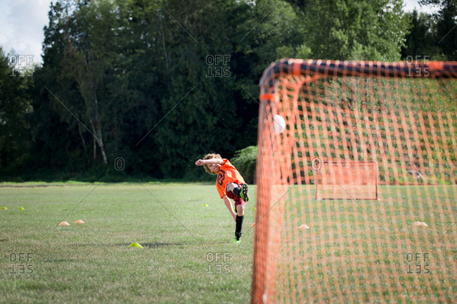 Boy kicking soccer ball toward goal