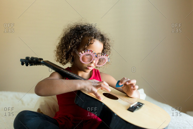 Little girl with silly glasses strumming guitar