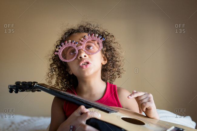 Little girl with silly glasses singing and playing guitar