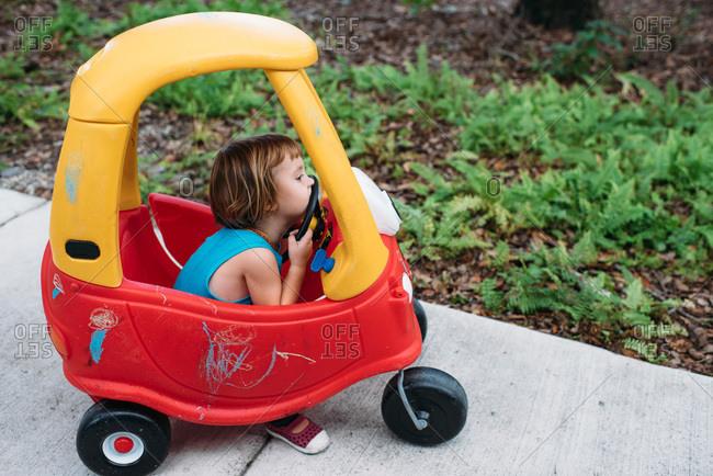 Toddler in toy plastic car on a sidewalk
