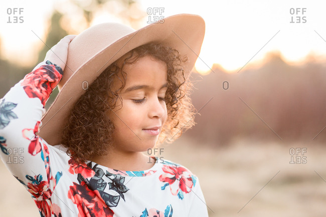 Little girl daydreaming outside in dress up clothes