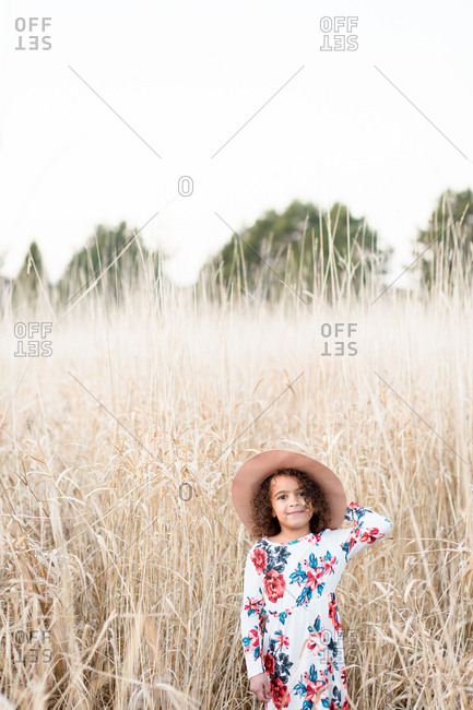 Girl happily playing dress up in large field of grass