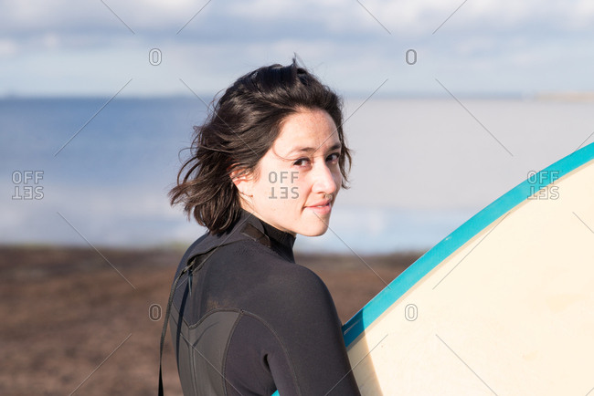 Woman wearing wet suit looking at back while carrying surfboard