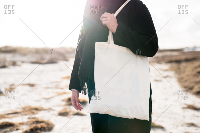 Woman on a beach carrying a tote
