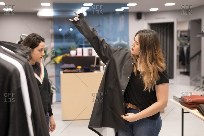 Two women trying on coats in a store