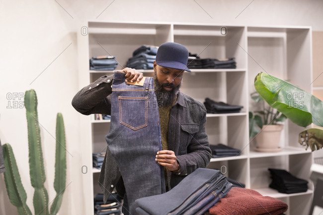 Hipster man shopping for jeans