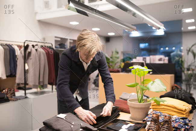 Hipster man shopping for jeans and using cell phone