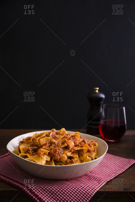 Pappardelle bolognese on a table with red wine