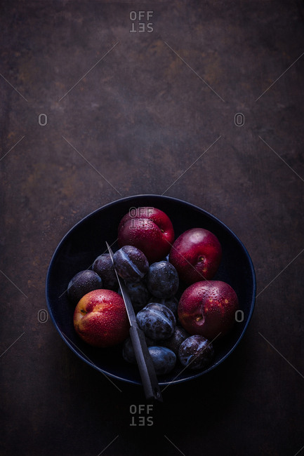 Overhead view of a bowl of fresh stone fruit
